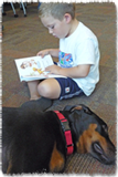 Boy reading on the floor next to a sleeping dog.